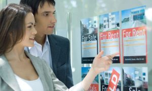 Couple looking at properties through window of estate agent