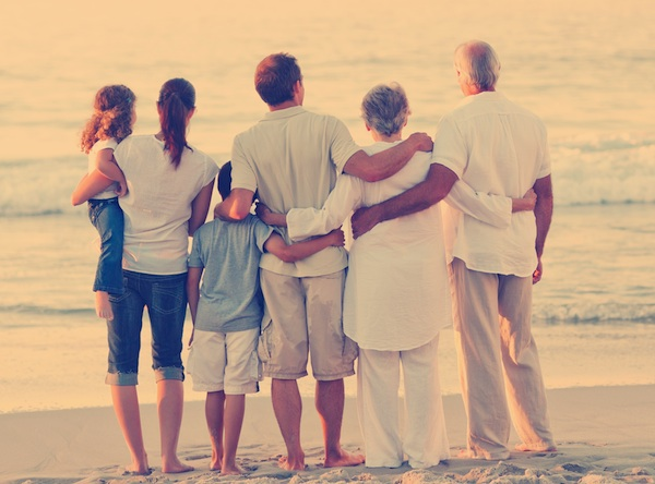 Family with arms around each other on beach